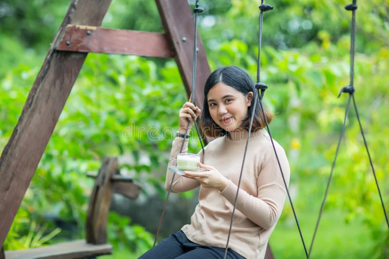Το ασιατικό κορίτσι στην ξύλινη ταλάντευση και απολαμβάνει με το πράσινο τσάι της στοκ εικόνες με δικαίωμα ελεύθερης χρήσης