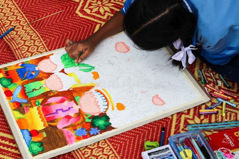 Το ασιατικό κορίτσι χρωματίζει το χρώμα κραγιονιών στο σχέδιό της για σύρει στοκ φωτογραφίες