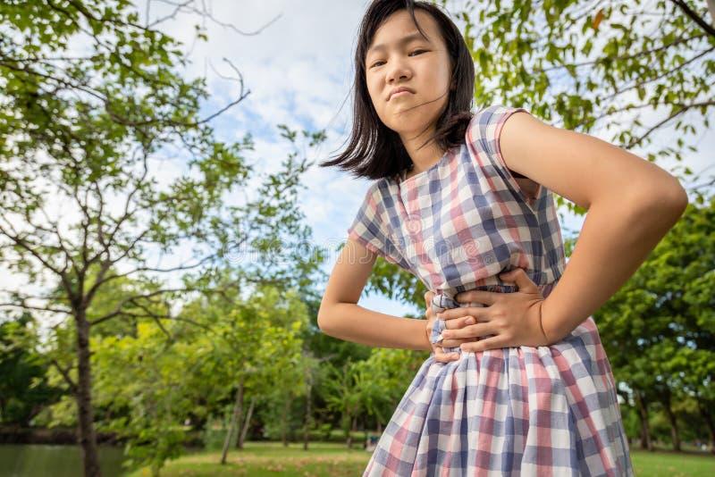 Το ασιατικό μικρό κορίτσι που κρατά τα χέρια της στην κοιλιά, στομαχόπονος, χαριτωμένο παιδί έχει τον κοιλιακό πόνο, άρρωστος πόν στοκ εικόνες με δικαίωμα ελεύθερης χρήσης