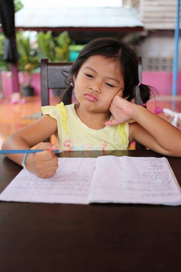 Το ασιατικό μολύβι χρήσης κοριτσιών παιδιών γράφει τις επιστολές στο βιβλίο στοκ εικόνες