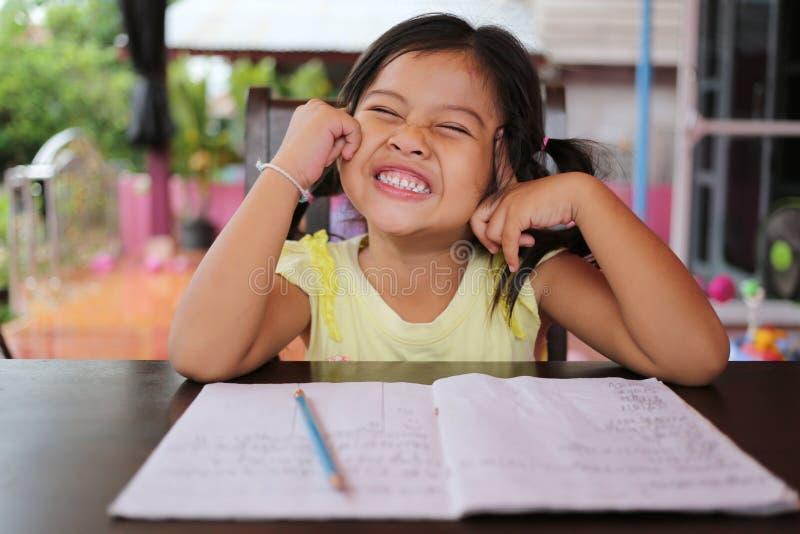 Το ασιατικό μολύβι χρήσης κοριτσιών παιδιών γράφει τις επιστολές στο βιβλίο στοκ εικόνες με δικαίωμα ελεύθερης χρήσης
