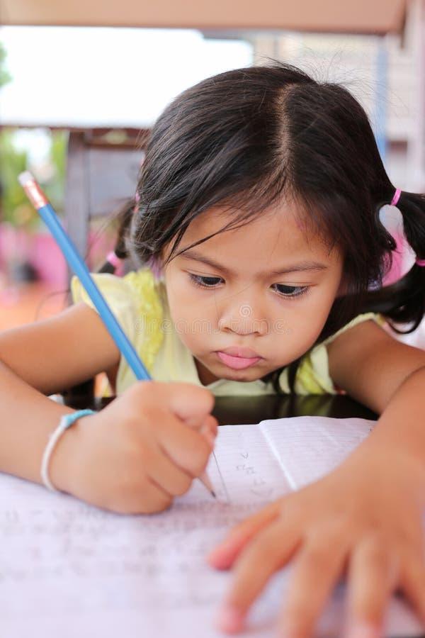 Το ασιατικό μολύβι χρήσης κοριτσιών παιδιών γράφει τις επιστολές στο βιβλίο στοκ εικόνα