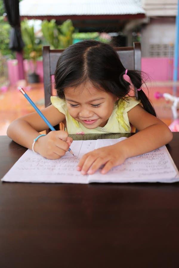 Το ασιατικό μολύβι χρήσης κοριτσιών παιδιών γράφει τις επιστολές στο βιβλίο στοκ εικόνα με δικαίωμα ελεύθερης χρήσης