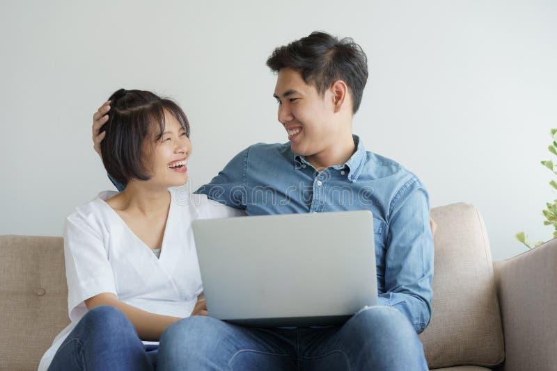 Το ασιατικό νέο ζεύγος κάνει τη διασκέδαση της εργασίας στο lap-top κάθονται στον καναπέ στο σύγχρονο καθιστικό στοκ φωτογραφίες