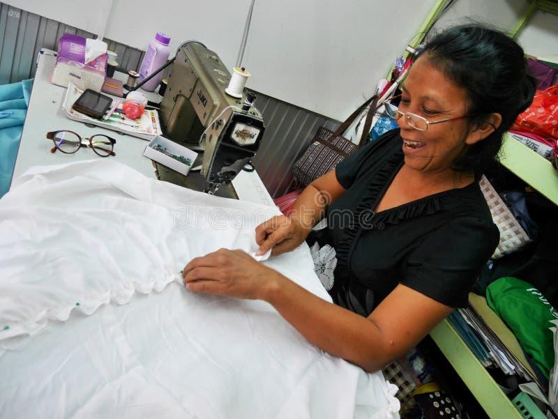 Το ασιατικό ταϊλανδικό ράψιμο μηχανών χρήσης ηλικιωμένων γυναικών και τα δημιουργικά ενδύματα σχεδίου διαμορφώνουν στο εργαστήριο στοκ φωτογραφίες με δικαίωμα ελεύθερης χρήσης