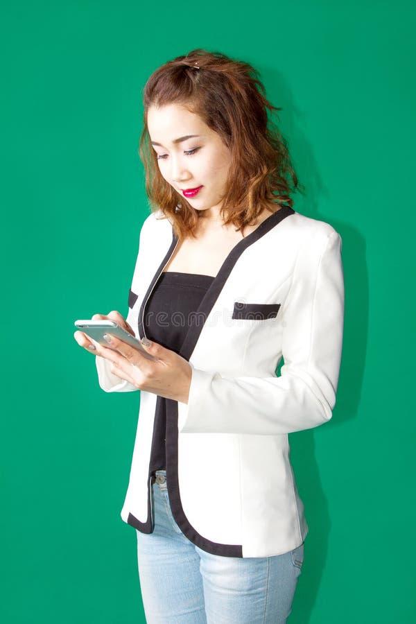 Το ασιατικό ταϊλανδικό κορίτσι στην επιχείρηση φαίνεται συζήτηση με το κινητό τηλέφωνο communic στοκ φωτογραφίες
