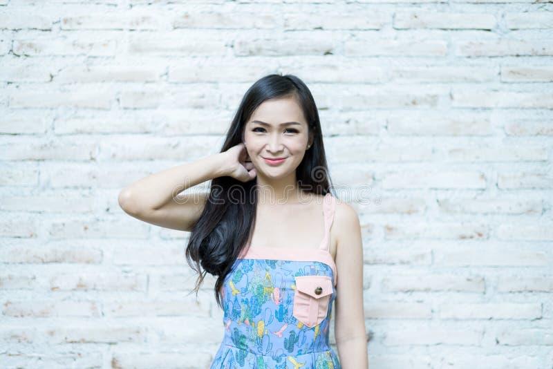Το ασιατικό όμορφο κορίτσι έχει την τοποθέτηση hipster της έννοιας με το υπόβαθρο τούβλου σε λίγο καφέ κήπων δέντρων, επαρχία Nak στοκ φωτογραφία με δικαίωμα ελεύθερης χρήσης