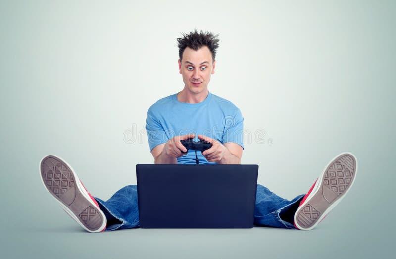 Το αστείο άτομο με ένα πηδάλιο κάθεται στο πάτωμα μπροστά από ένα lap-top Παιχνίδια Gamer στοκ εικόνα με δικαίωμα ελεύθερης χρήσης