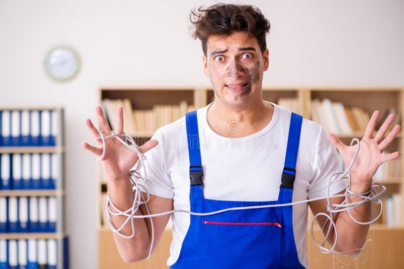 Το αστείο άτομο που κάνει τις ηλεκτρικές επισκευές στο σπίτι στοκ εικόνες