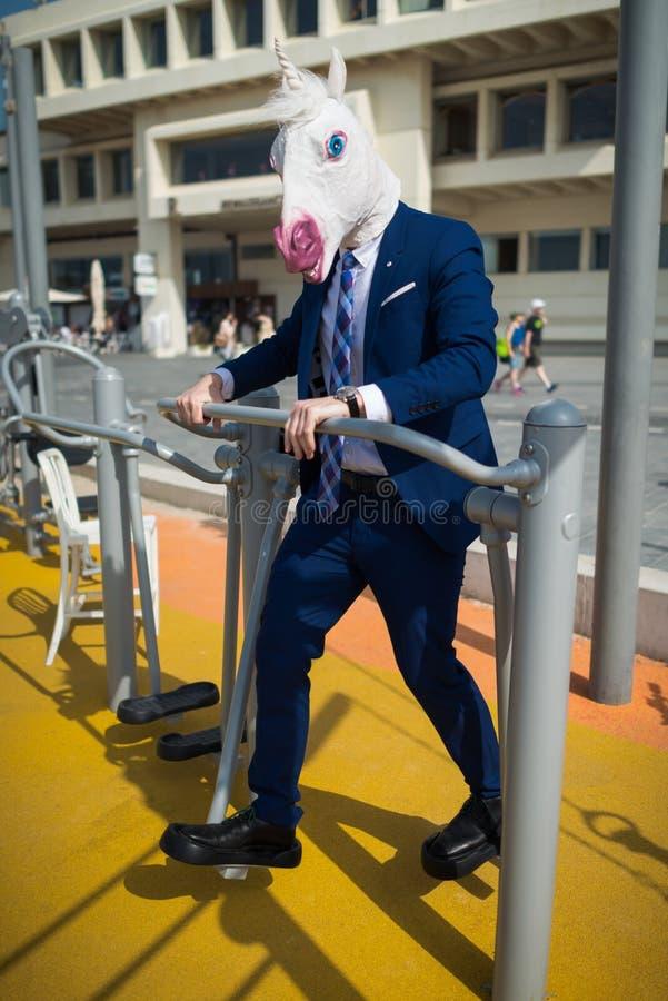 Το αστείο άτομο στο κομψό κοστούμι και την κωμική μάσκα κάνει τις αθλητικές ασκήσεις στοκ εικόνες