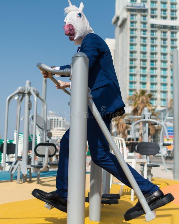 Το αστείο άτομο στο κομψό κοστούμι και τη freaky μάσκα κάνει τις αθλητικές ασκήσεις στοκ φωτογραφία με δικαίωμα ελεύθερης χρήσης