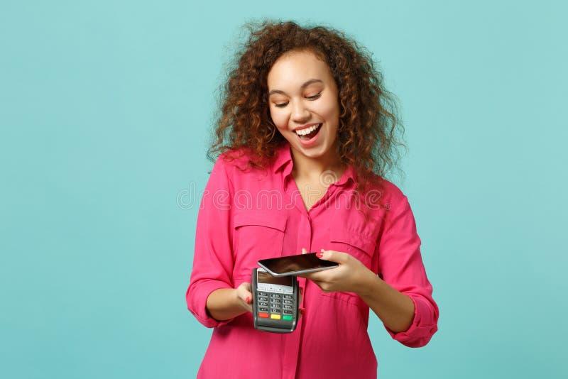 Το αστείο αφρικανικό κοριτσιών τερματικό πληρωμής τηλεφωνικών ασύρματο σύγχρονο τραπεζών λαβής κινητό στη διαδικασία, αποκτά τις  στοκ φωτογραφία