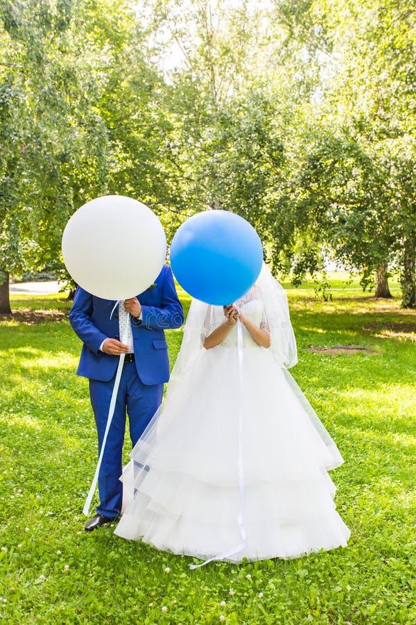 Το αστείο γαμήλιο ζεύγος με τα μπαλόνια, που στέκονται σε ένα λιβάδι και έχει τη διασκέδαση στοκ εικόνα με δικαίωμα ελεύθερης χρήσης