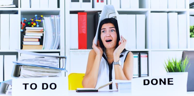 Το αστείο καταπονημένο κορίτσι με έναν φάκελλο στην επικεφαλής συνεδρίασή της στον εργασιακό χώρο σωρίασε με τους φακέλλους Αντίδ στοκ φωτογραφία