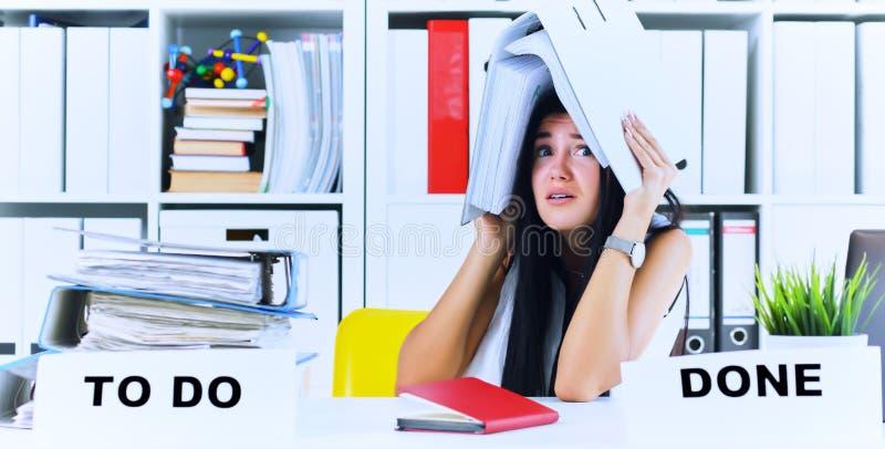 Το αστείο καταπονημένο κορίτσι με έναν φάκελλο στην επικεφαλής συνεδρίασή της στον εργασιακό χώρο σωρίασε με τους φακέλλους Αντίδ στοκ φωτογραφίες