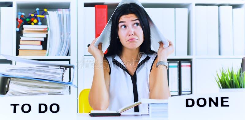 Το αστείο καταπονημένο κορίτσι με έναν φάκελλο στην επικεφαλής συνεδρίασή της στον εργασιακό χώρο σωρίασε με τους φακέλλους Αντίδ στοκ εικόνες