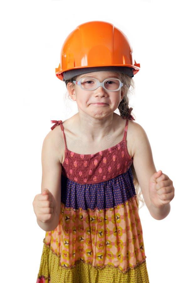 Το αστείο κορίτσι κόκκινο hardhat clenchs οι πυγμές της στοκ φωτογραφία