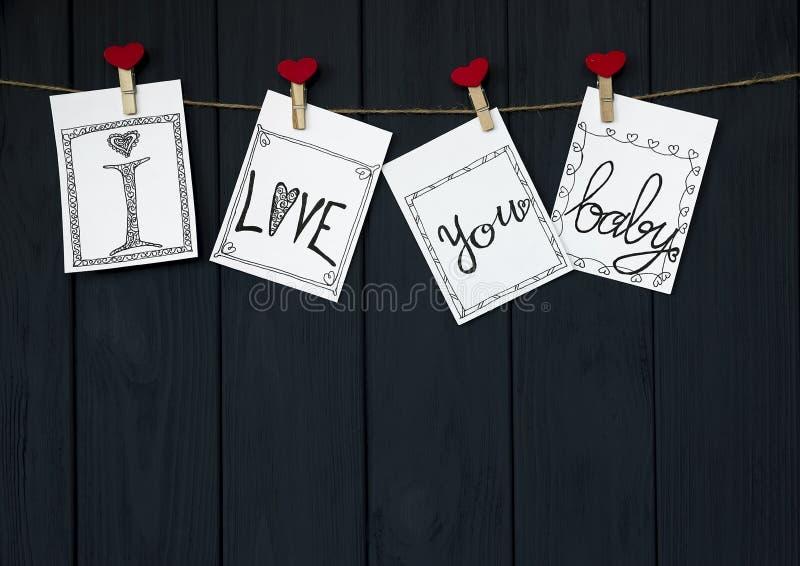 Το αστείο μήνυμα στις τέσσερις κάρτες βαλεντίνων ` s λέει ` σ' αγαπώ, μωρό! ` φυσικό σκοινί και κόκκινες καρφίτσες που κρεμούν στ στοκ φωτογραφία με δικαίωμα ελεύθερης χρήσης