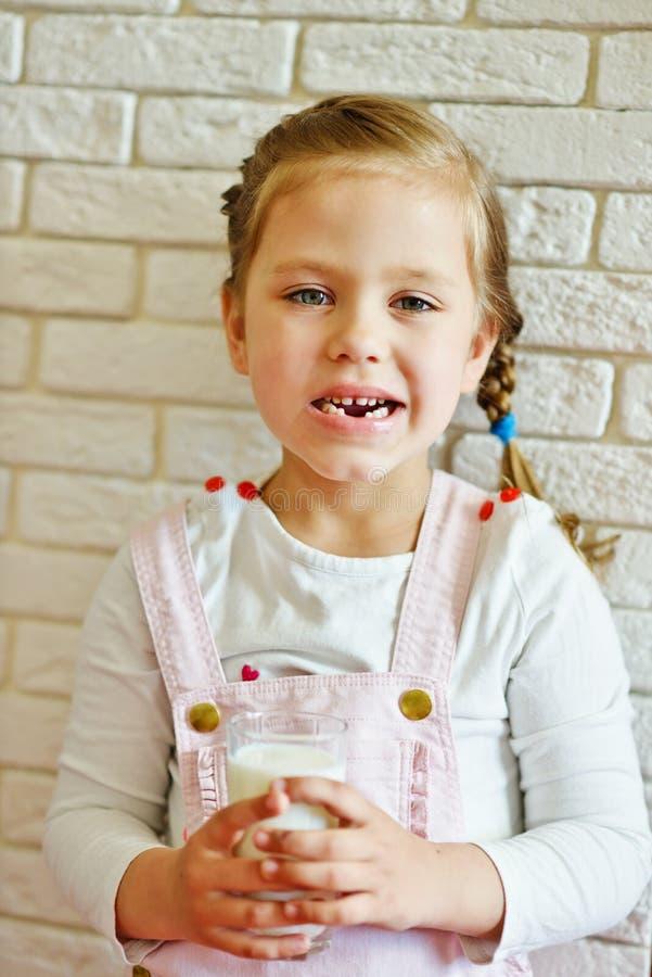 Το αστείο μικρό κορίτσι έχασε το δόντι γάλακτός της στοκ εικόνες