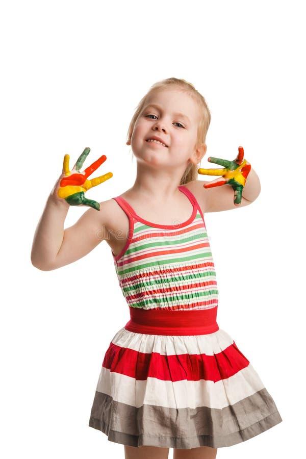 Το αστείο μικρό κορίτσι με τα χέρια χρωμάτισε στο ζωηρόχρωμο χρώμα απομονωμένος στοκ εικόνα