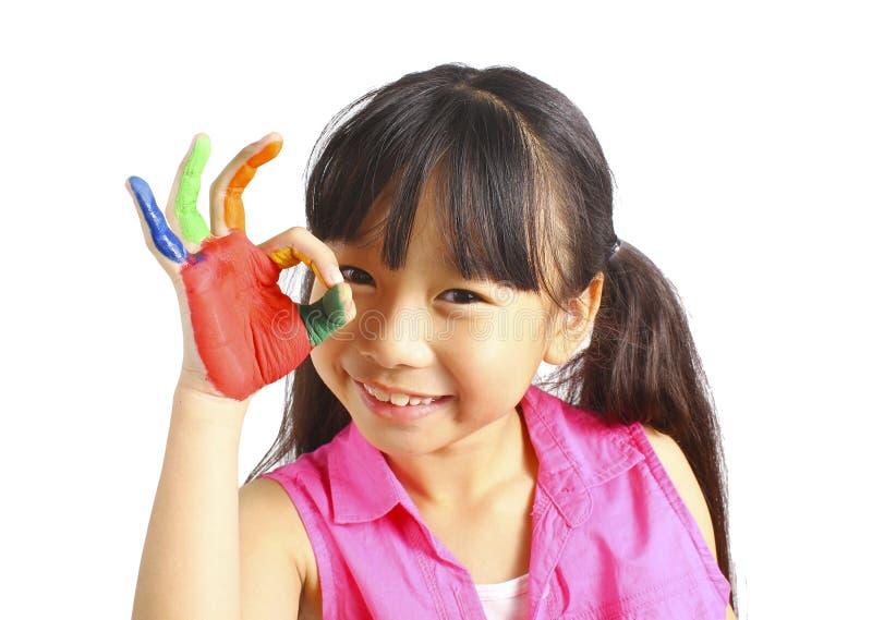 Το αστείο μικρό κορίτσι με τα χέρια χρωμάτισε στο ζωηρόχρωμο χρώμα στοκ εικόνα με δικαίωμα ελεύθερης χρήσης