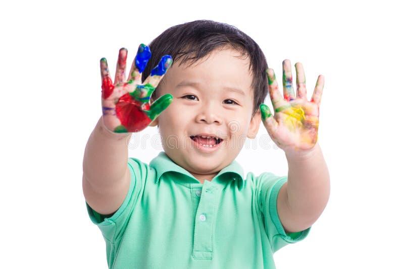 Το αστείο μικρό παιδί με τα χέρια χρωμάτισε στο ζωηρόχρωμο χρώμα η ανασκόπηση απομόνωσε το λευκό στοκ φωτογραφία με δικαίωμα ελεύθερης χρήσης