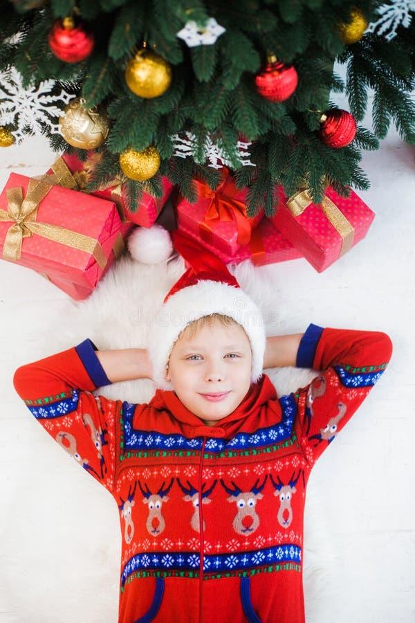 Το αστείο παιδάκι έντυσε στις κόκκινα πυτζάμες και το καπέλο του santa στοκ φωτογραφία με δικαίωμα ελεύθερης χρήσης