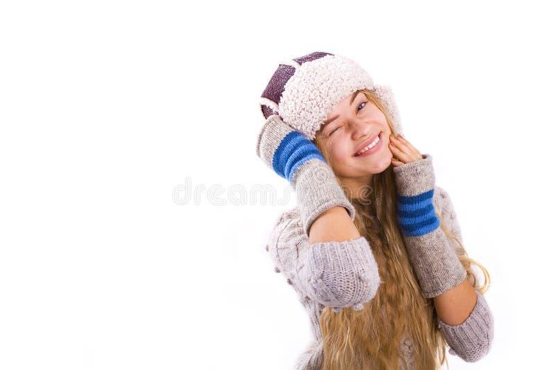 Το αστείο όμορφο κορίτσι κλείνει το μάτι σε ένα άσπρο υπόβαθρο στοκ φωτογραφία