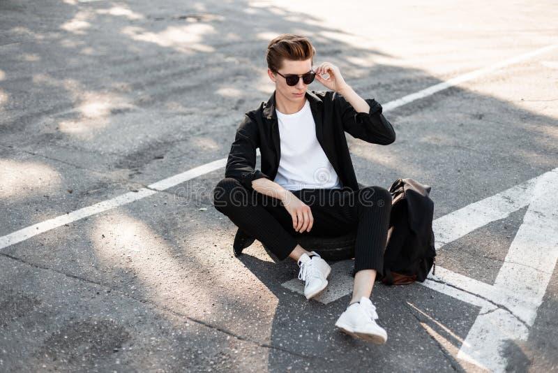 Το αστικό νέο άτομο hipster με το hairstyle στα γυαλιά ηλίου σε ένα μαύρο πουκάμισο στα καθιερώνοντα τη μόδα ριγωτά εσώρουχα στα  στοκ εικόνα
