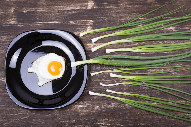 Το αυγό, τα φρέσκα κρεμμύδια και το μαύρο πιάτο, κλείνουν επάνω στοκ εικόνα