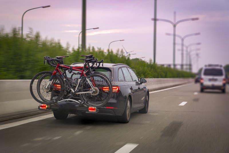 Το αυτοκίνητο μεταφέρει ποδήλατα σε ένα rack στην εθνική οδό νωρίς το πρωί στοκ φωτογραφίες με δικαίωμα ελεύθερης χρήσης