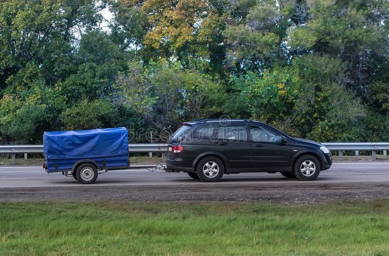 Το αυτοκίνητο με το ρυμουλκό πηγαίνει στην εθνική οδό στοκ φωτογραφία