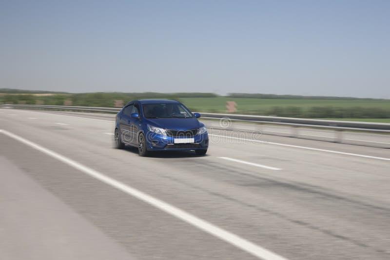 Το αυτοκίνητο οδηγά γρήγορα στην εθνική οδό στοκ εικόνα