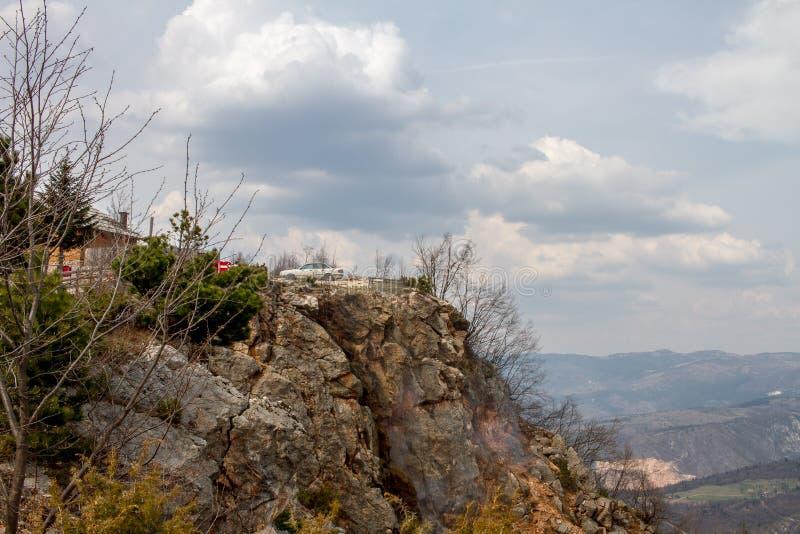 Το αυτοκίνητο που σταθμεύουν σε έναν απότομο βράχο καλύπτει τα ανωτέρω και όμορφα ορόσημα φύσης γύρω στοκ φωτογραφία με δικαίωμα ελεύθερης χρήσης
