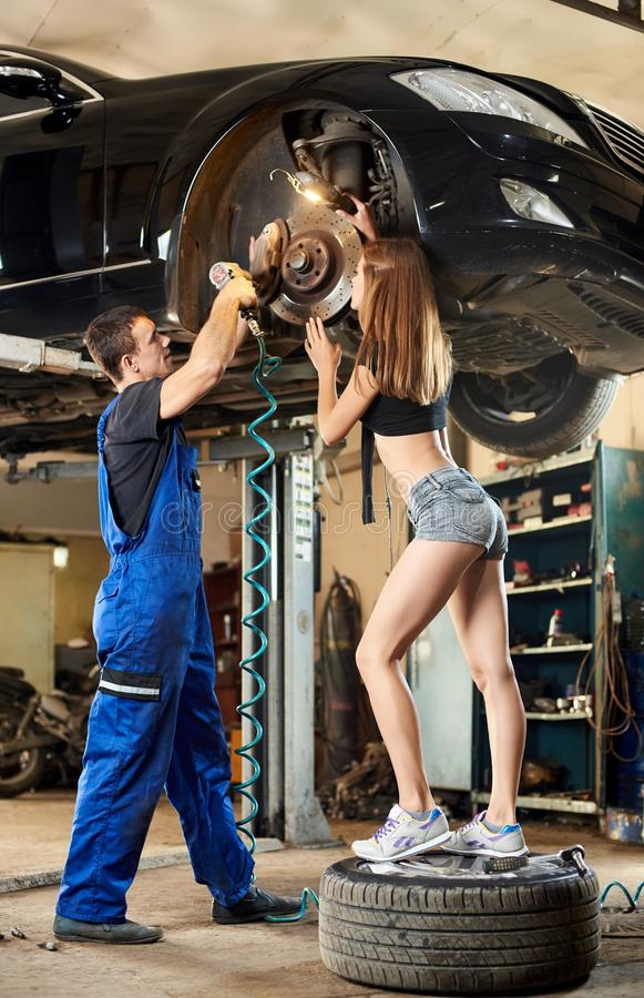 Το αυτοκίνητο στο υδραυλικό κορίτσι τύπων ανελκυστήρων τον επιθεωρείται στοκ εικόνα με δικαίωμα ελεύθερης χρήσης