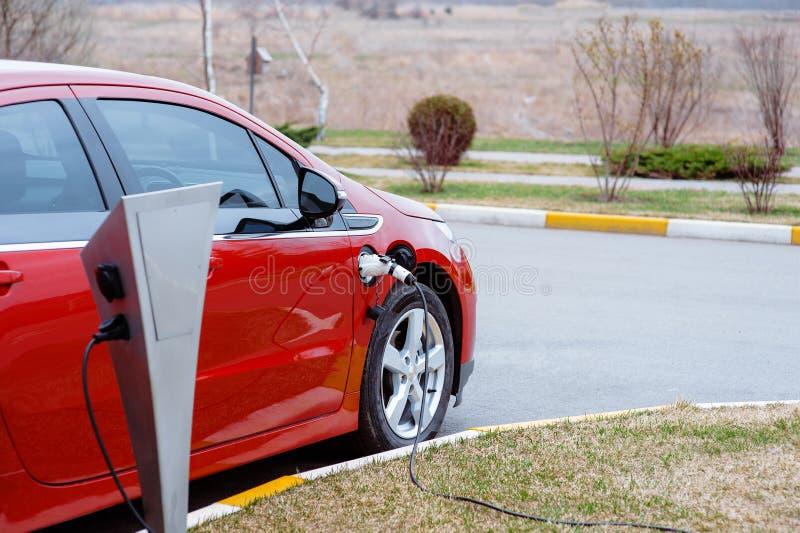 Το αυτοκίνητο της EV ή το ηλεκτρικό κόκκινο αυτοκίνητο στο σταθμό χρέωσης με τον ανεφοδιασμό καλωδίου τροφοδοσίας σύνδεσε στη θολ στοκ εικόνες με δικαίωμα ελεύθερης χρήσης