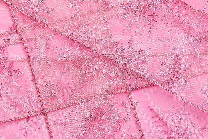 Το αφηρημένο κατασκευασμένο υπόβαθρο της ρόδινης καθαρής κορδέλλας με ακτινοβολεί snowflakes στοκ φωτογραφίες