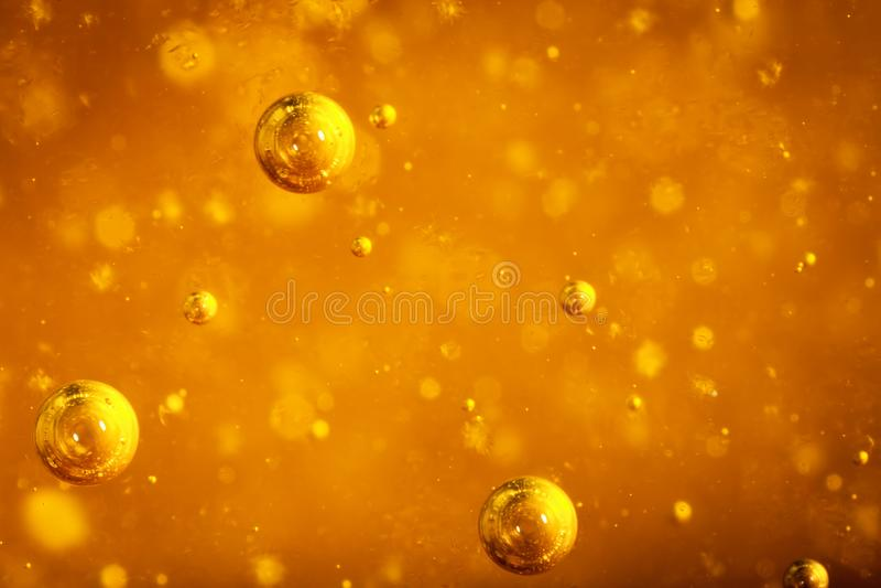 Το αφηρημένο μακρο μέλι βράζει κινηματογράφηση σε πρώτο πλάνο στο φωτεινό ηλέκτρινο χρώμα Η σύσταση του μελιού τρόφιμα έννοιας υγ στοκ εικόνες