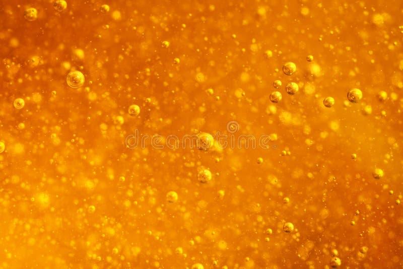 Το αφηρημένο μακρο μέλι βράζει κινηματογράφηση σε πρώτο πλάνο στο φωτεινό ηλέκτρινο χρώμα Η σύσταση του μελιού τρόφιμα έννοιας υγ στοκ φωτογραφία με δικαίωμα ελεύθερης χρήσης