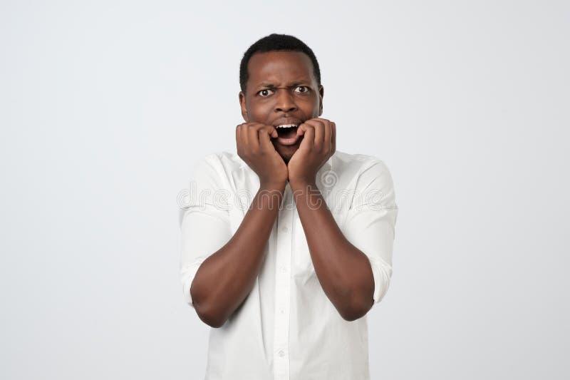 Το αφρικανικό άτομο με τη νευρική έκφραση, καρφιά δάχτυλων δαγκωμάτων, ανησυχεί πριν από τη συνέντευξη στοκ εικόνα