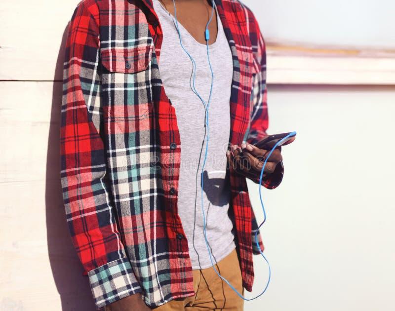 Το αφρικανικό άτομο μόδας ακούει τη μουσική σε ένα smartphone στοκ εικόνες