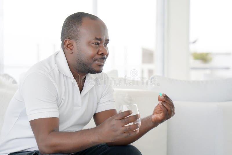 Το αφρικανικό άτομο πίνει ένα χάπι από τον πόνο στοκ εικόνες