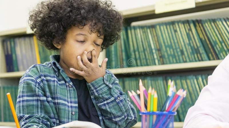 Το αφρικανικό αγόρι κάθεται και μαθαίνοντας έχει τη βουλομένη μύτη στοκ εικόνες με δικαίωμα ελεύθερης χρήσης