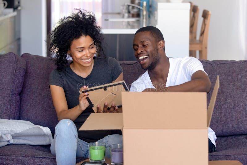 Το αφρικανικό ζεύγος ανοίγει τις περιουσίες στην κίνηση της ημέρας στο καινούργιο σπίτι στοκ εικόνες