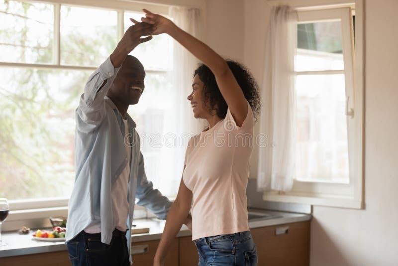 Το αφρικανικό ζεύγος που στέκεται στην κουζίνα που χορεύει αισθάνεται ευτυχές στοκ φωτογραφίες
