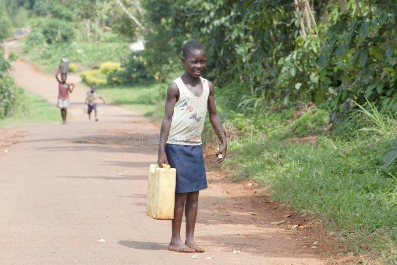 Το αφρικανικό κορίτσι παίρνει το σπίτι νερού στοκ εικόνες