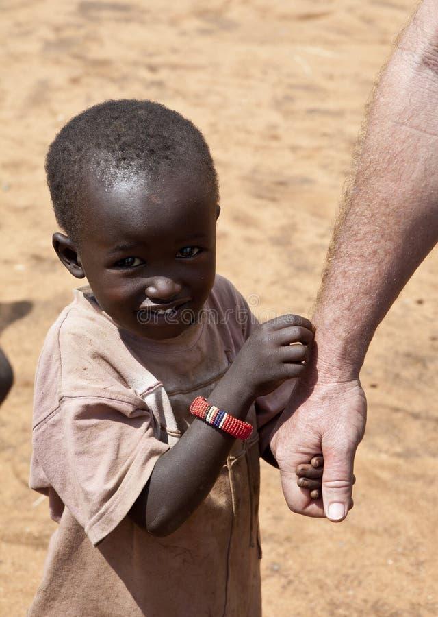 Το αφρικανικό παιδί κρατά το χέρι του εργαζομένου ενίσχυσης στοκ εικόνα