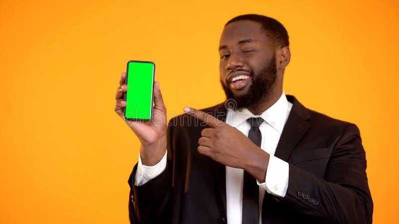 Το αφροαμερικανός αρσενικό στο κοστούμι που δείχνει το τηλέφωνο και το κλείσιμο του ματιού, διαφήμιση στοκ φωτογραφίες