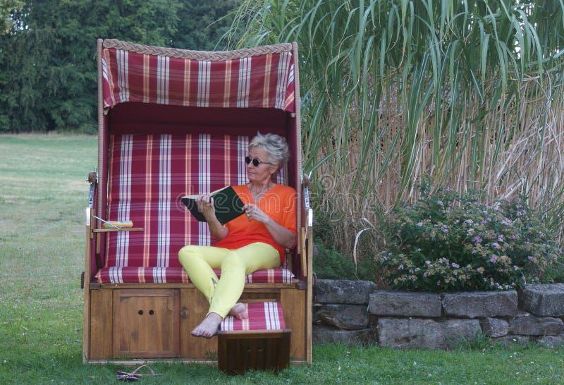 Το Α η ψάθινη καρέκλα παραλιών και ένα βιβλίο, για την ελκυστική γυναίκα οι χρονικές στάσεις ακόμα στοκ φωτογραφία