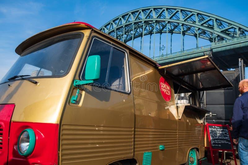 Το Α το κλασικό φορτηγό χρησιμοποιείται ως φορητή εξυπηρετώντας πίτσα καντίνων σε Gateshead, Νιουκάσλ με τη γέφυρα Τάιν στο υπόβα στοκ εικόνα